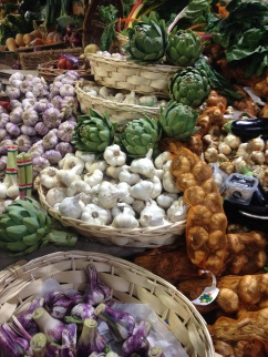 Garlics, onions and artichokes at the Rialto Market, Venice.